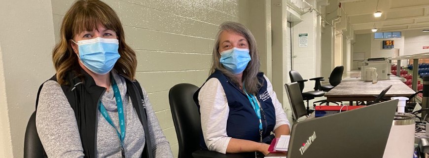two masked staff members working at covid vaccine clinic