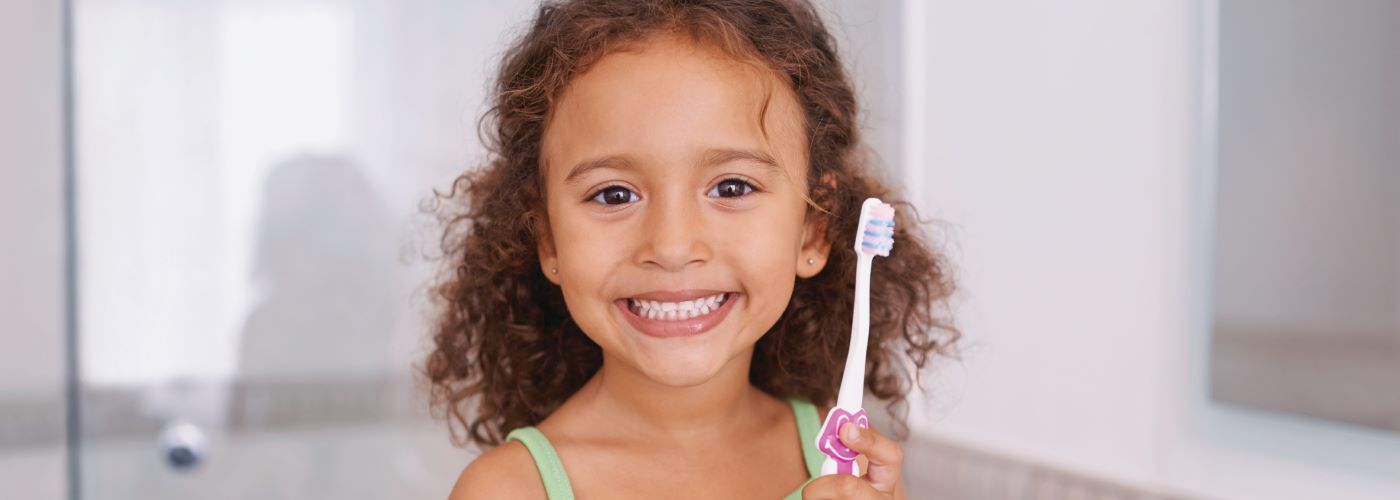 young girl smiling holding tooth brush
