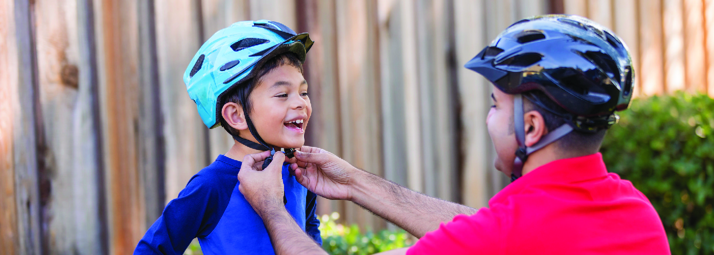 dad putting a bike helmet on his son