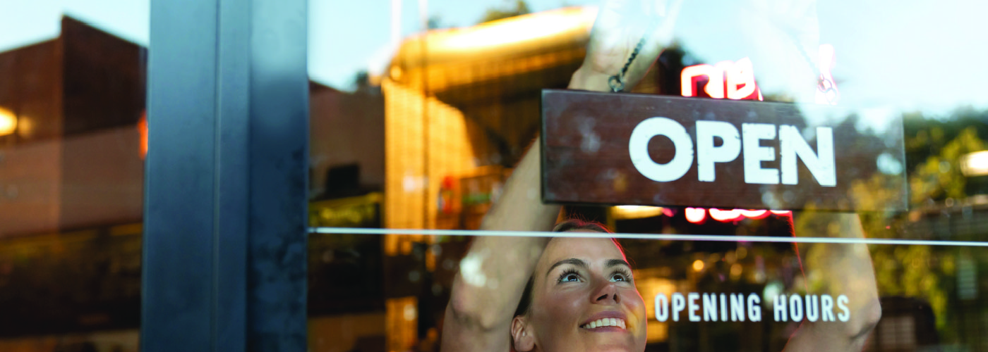 Woman hanging an open sign in restaurant window