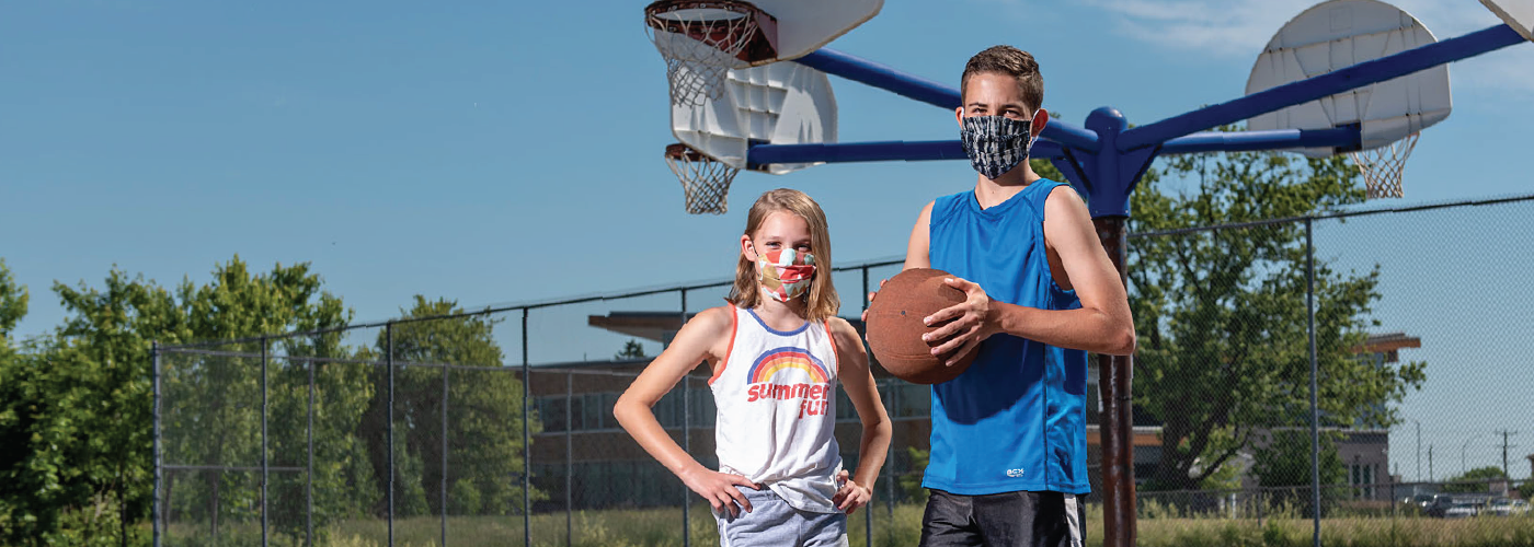 Young boy and girl wearing masks playing basketball