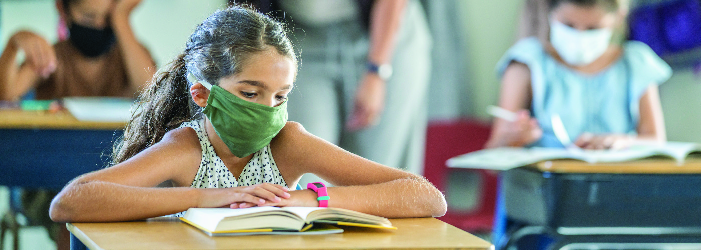 Young girl in school wearing a mask