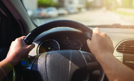 Person with hands on steering wheel of car