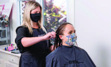 Hair stylist cutting a woman's hair while wearing a mask
