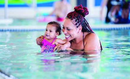 Women swimming with toddler daughter