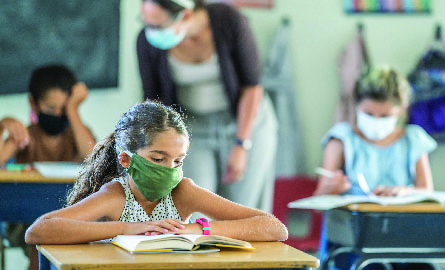 Young girl wearing mask sitting at school desk in a classroom