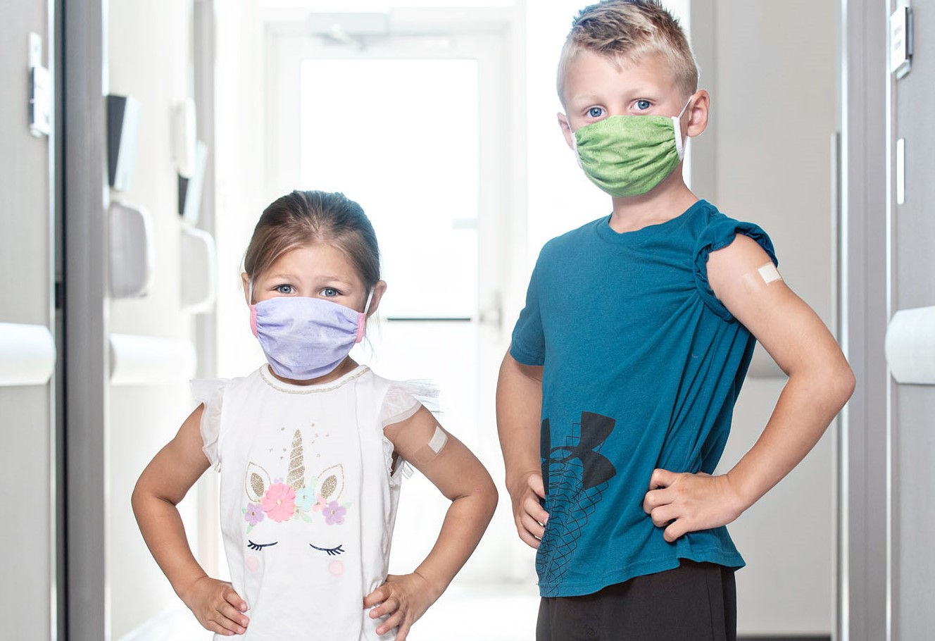 Young boy and girl wearing masks after receiving flu shots
